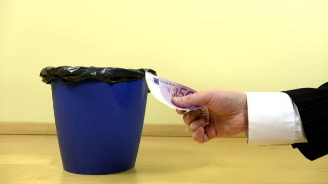 hand crumple five hundred 500 euro banknote and drop in bin.