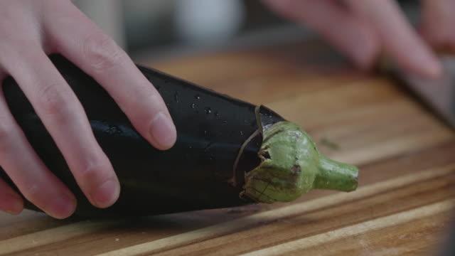 hand cut aubergine on wooden chopping board - melanzane video stock e b–roll