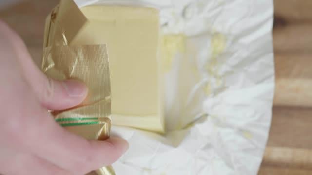 vídeos de stock, filmes e b-roll de mão cortada bloco manteiga em cubos - gordura