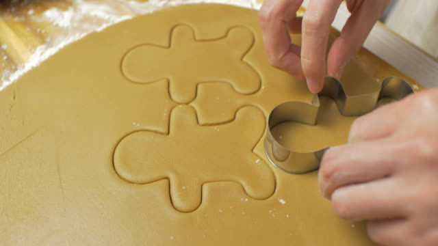 hand cut gingerman bread on wooden cutting board close up view of hand cut gingerman bread at home kitchen cookie cutter stock videos & royalty-free footage