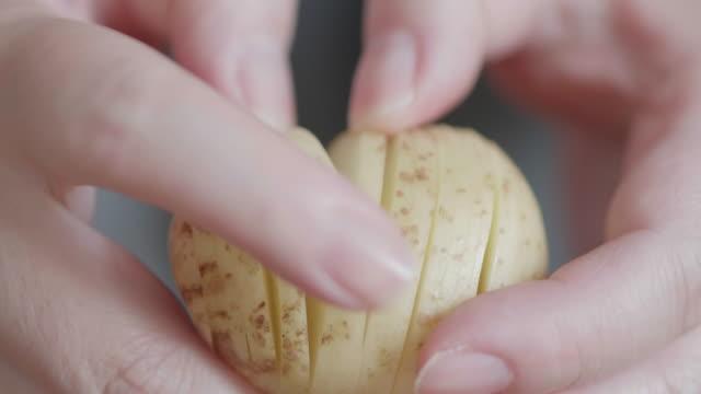 hand cut raw new potato for making hasselback potato - молодой картофель стоковые видео и кадры b-roll