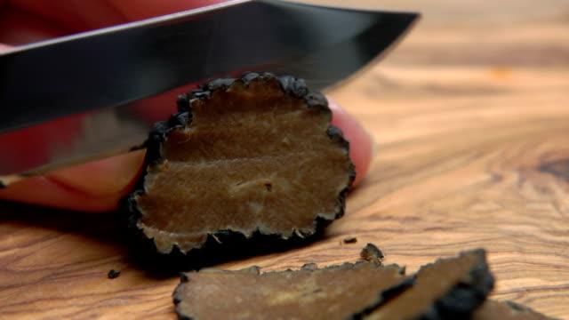hand schneidet schwarzen trüffel mit einem messer in eine scheibe - knollig stock-videos und b-roll-filmmaterial