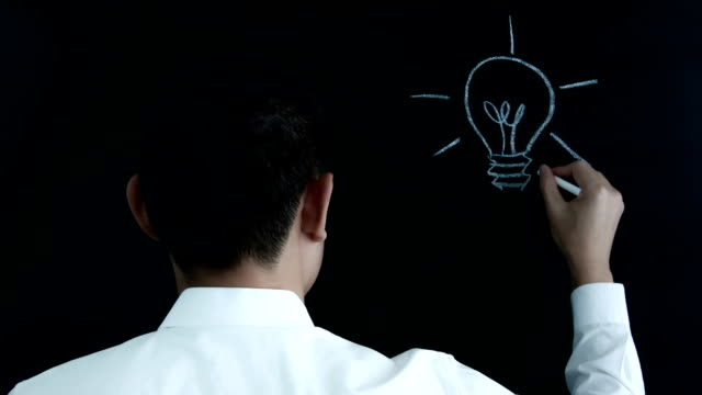 Hand drawing a lightbulb on chalkboard. video