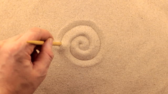 Hand drawing on a rotating sand, spiral. video
