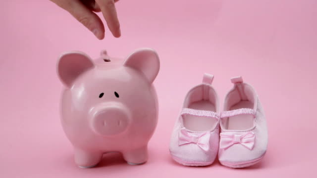 Hand dropping coin in piggy bank Hand dropping coin in piggy bank with baby booties in pink baby booties stock videos & royalty-free footage