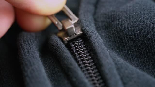 Hand fastens a black plastic zipper lock on grey blue sports jacket