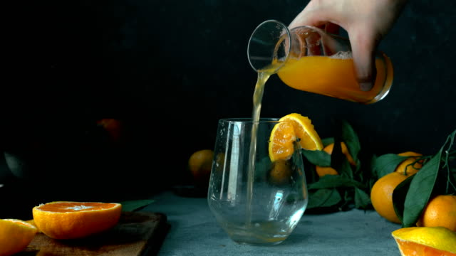 Hand Gently Pour Tangerine / Orange Juice From Vintage Bottle into a Glass Pouring orange juice or mandarin juice into glass. Rustic concept. orange juice stock videos & royalty-free footage