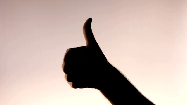 Hand gesture. Thumbs up. Silhouetted male hand on gradient pink background
