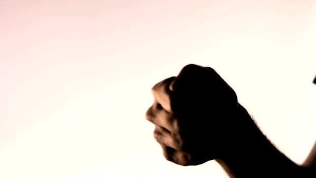 Hand gesture. Thumbs up. Silhouetted male hand on gradient pink background video