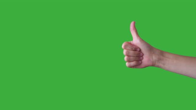 el eller gibi ve üzerinde yeşil arka plan sevmemek - thumbs up stok videoları ve detay görüntü çekimi