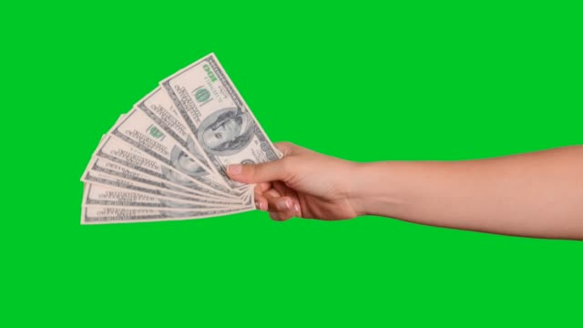 Hand giving money Hand giving American dollars on chroma key green screen. paper currency stock videos & royalty-free footage