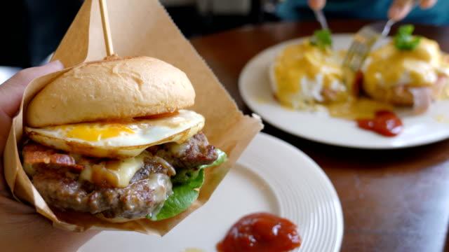 hand greppa en hamburgare och äta. - hamburgare bildbanksvideor och videomaterial från bakom kulisserna
