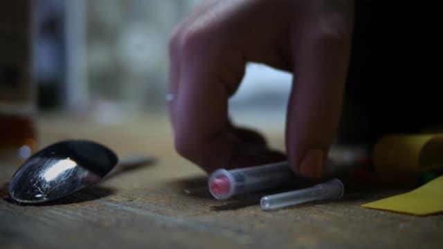 hand griper en spruta från grungy golv - drug addiction heroin koncept - missbruk koncept bildbanksvideor och videomaterial från bakom kulisserna