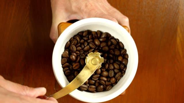 handschleifmaschine, geröstete kaffeebohnen mit hand-schleifer draufsicht in selektiven fokus. closeup gesperrt schuss. slow-motion. - grind stock-videos und b-roll-filmmaterial