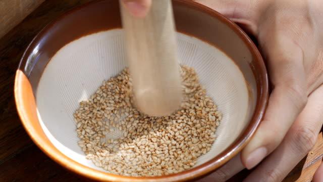 macinazione a mano di semi di sesamo bianco per il cibo giapponese. - sesamo video stock e b–roll