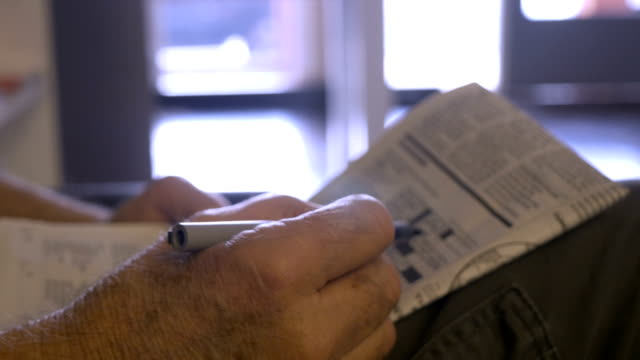 Hand held close up of a senior hand working a crossword puzzle in a newspaper