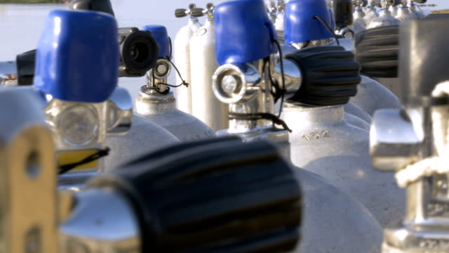 Hand held closeup of multipul scuba diving cylinder tanks Hand held closeup of a number of scuba diving cylinder tanks lined up on the beach. aqualung diving equipment stock videos & royalty-free footage