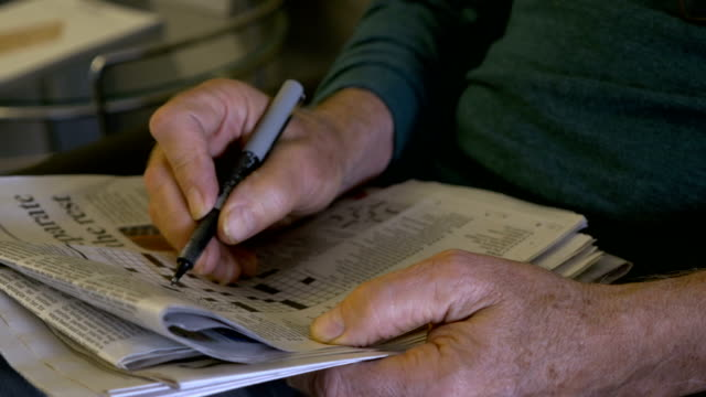 Hand held of an elderly man filling out a crossword puzzle with a pen