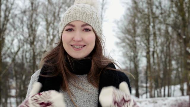ручной выстрел. красота радостная модель девушка смеется и весело провести время в зимнем парке. красивая молодая женщина на открытом возд� - уход за телом стоковые видео и кадры b-roll