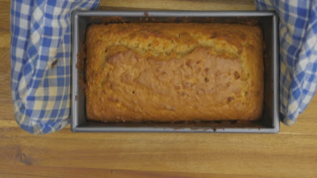 hand hold fresh baked cake in the tin and put on the table