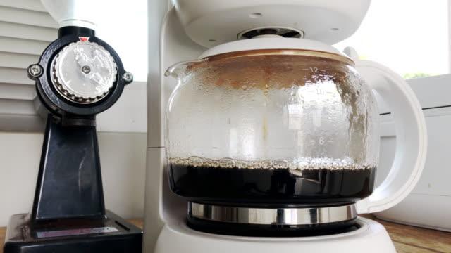рука, держащая чашку капельного кофеварка вместе, чтобы сделать кофе. - кофеин стоковые видео и кадры b-roll