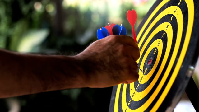 Hand holding a darts out from the goal.  New start and Business solution concept. retry until it is successful