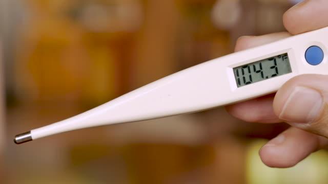 stockvideo's en b-roll-footage met hand die een digitale thermometer houdt die 104.3 graden fahrenheit - close-up toont - thermometer