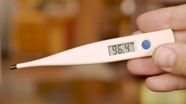 Hand holding a digital thermometer with the temperature 96.7 degrees fahrenheit