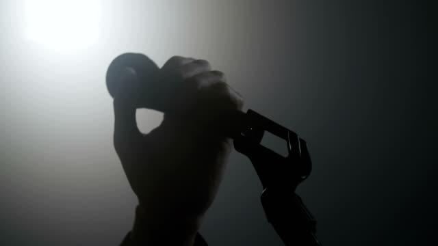 tenere a mano un microfono - cantante video stock e b–roll