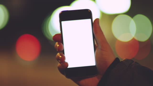 CU Hand holding a smartphone in city at night video