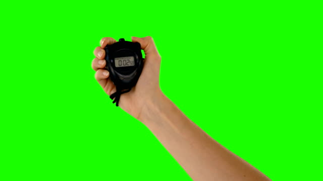 Hand holding a stopwatch Hand holding a stopwatch on a green background instrument of time stock videos & royalty-free footage