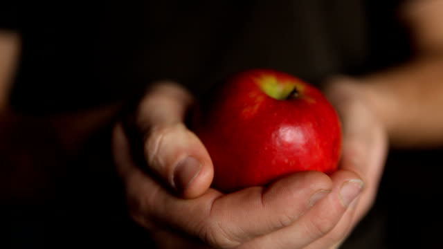 Hand holding an Apple offers it to viewer HD video