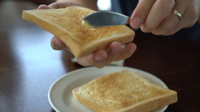 Hand holding bread and butter making for breakfast video