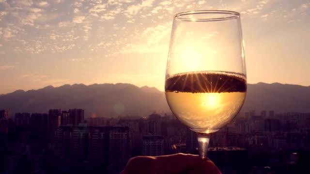 hand hållande champagne vid solnedgången - vitt vin glas bildbanksvideor och videomaterial från bakom kulisserna