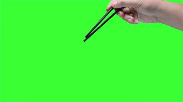 Hand holding chopsticks on green screen background Hand holding chopsticks on green screen background handful stock videos & royalty-free footage