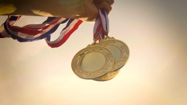 金メダルを手に持つ - メダル点の映像素材/bロール