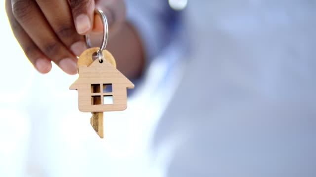 handhalteschlüssel aus haus, immobilienvermietung oder -kauf, hypothekenbankkredit - hausschlüssel stock-videos und b-roll-filmmaterial