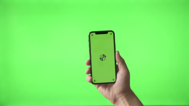 Hand Holding Modern Smartphone on Green Screen BG