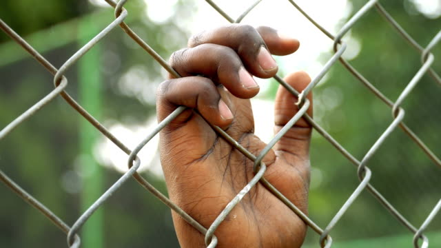 Hand holding on chainlink fence