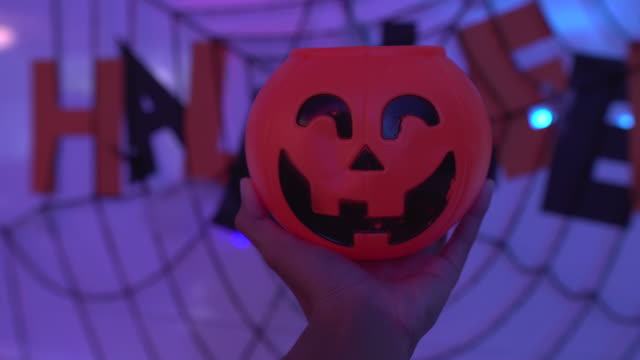Hand holding scary pumpkin bowl on halloween party