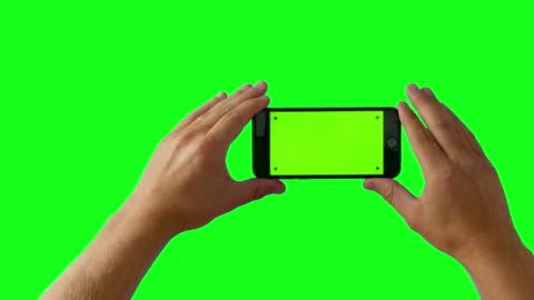 smartphone con mano su schermo verde bg - 4k - filmare video stock e b–roll