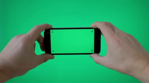 smartphone con mano (orizzontale) su green screen bg - filmare video stock e b–roll
