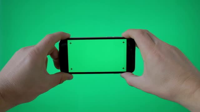 손을 잡고 (가로) 스마트폰 그린 스크린 bg에 - 영화 촬영 스톡 비디오 및 b-롤 화면