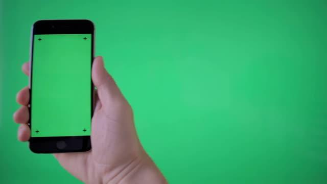 손을 잡고 (세로) 스마트폰 그린 스크린 bg에 - hand holding phone 스톡 비디오 및 b-롤 화면