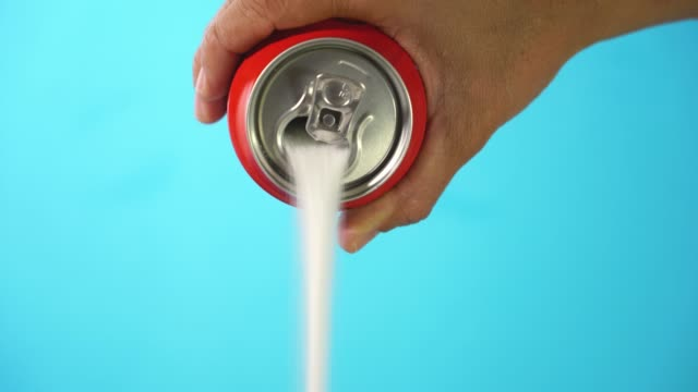 Hand holding soda can pouring lots of sugar in metaphor of sugar content of a refresh drink in healthy nutrition, diet, sweet and carbonated drinks addiction and unhealthy food concept. Hand holding soda can pouring lots of sugar in metaphor of sugar content of a refresh drink in healthy nutrition, diet, sweet and carbonated drinks addiction and unhealthy food concept blue background soda stock videos & royalty-free footage
