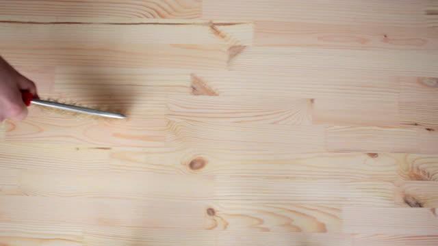 Hand holding steel brush Brushing Wood video