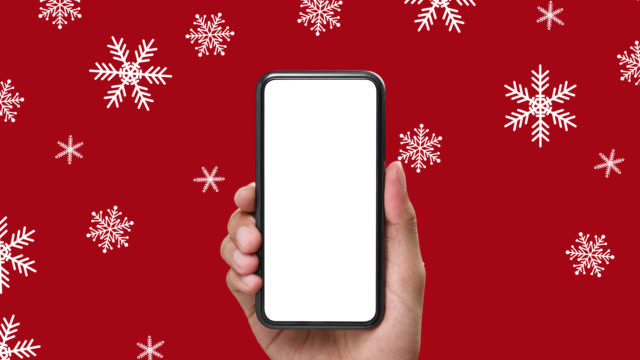 Hand holding the smartphone with white screen on snowflakes background