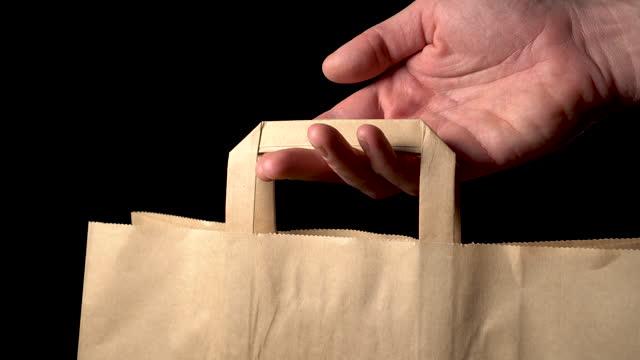 손으로 잡고 종이 봉투를 제공합니다. - black friday 스톡 비디오 및 b-롤 화면