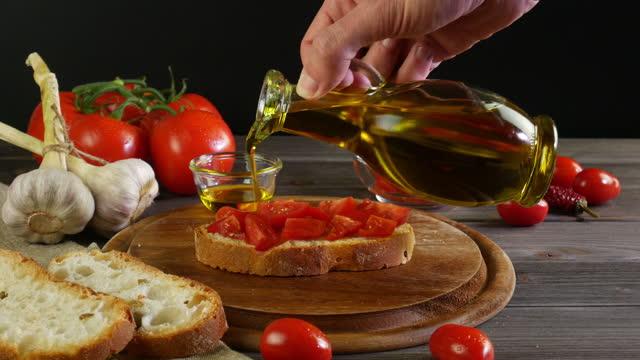 vídeos de stock, filmes e b-roll de mão segura garrafa de azeite, derrama azeite extra virgem em bruschetta com tomate, mesa com ingredientes da cozinha italiana mediterrânea no fundo preto - comida italiana