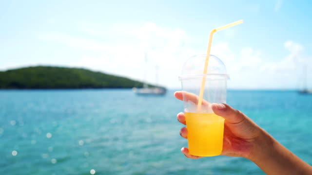 Hand holds cup of fresh orange juice Human hand holding cup of fresh orange juice with amazing blue sea in background. straw stock videos & royalty-free footage
